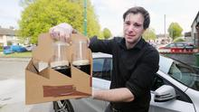Richard Grainger delivers pints of Guinness to customer Billy Scully (Niall Carson/PA)