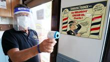 John O'Loughlin, owner of Tallaght Traditional Barber Shop, holds an infrared thermometer at his premises in Dublin (Brian Lawless/PA)