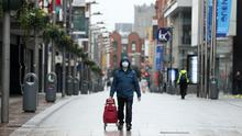 A shopper in a facemask walks down an almost deserted Henry Street in Dublin's city centre (PA)