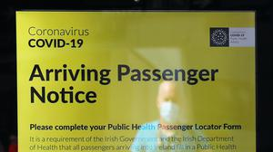 A notice for arriving passengers regarding the Covid-19 Passenger Locator Form (Brian Lawless/PA)