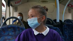 A school pupil wearing a face mask on a bus (Owen Humphreys/PA)