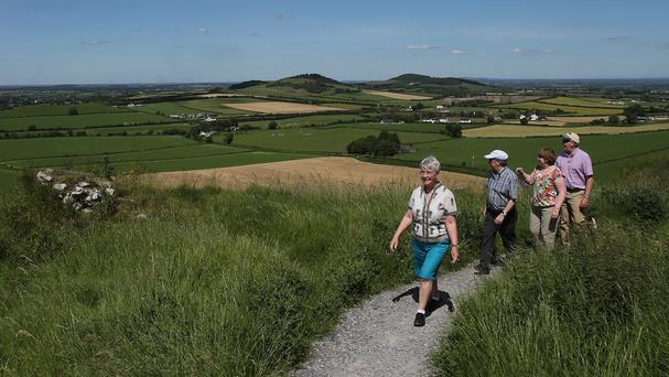 Hill walkers enjoy the view from The Rock of Dunamase, County Laois, during a period of hot weather.