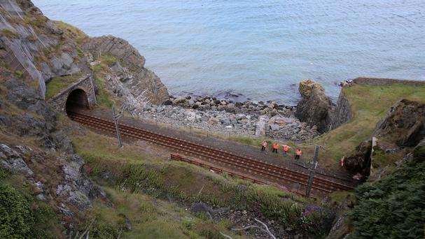 Irish Rail workers at the scene where a DART commuter train derailed near Bray after it struck a boulder.