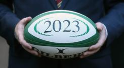 Enda Kenny holds a rugby ball during the launch of an all-Ireland bid to host the 2023 Rugby World Cup