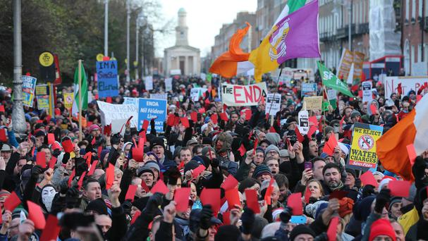 Crowds show red cards to the Government during the Right2Water anti-water charges protest outside Leinster House in Dublin last December