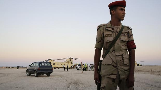 An Egyptian soldier stands guard as emergency workers unload bodies of victims from the crash of a Russian aircraft over the Sinai Peninsula (AP)