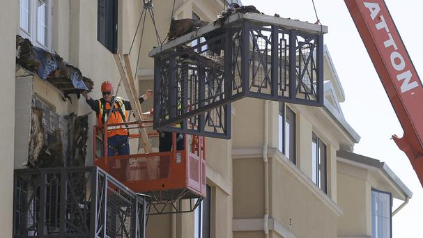 Workers remove part of a balcony that collapsed at the Library Gardens apartment complex in Berkeley, California (AP)