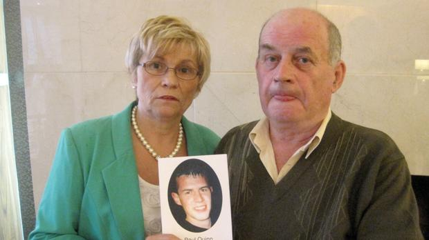 Stephen and Breege Quinn hold a picture of their murdered son Paul