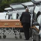 Coffins are taken to hearses at the scene in Oakdene, Barconey, Ballyjamesduff in Cavan