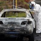 A forensic officer photographs a burnt-out car close to the scene of a fatal shooting in Griffeen Valley Park, Dublin