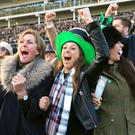 Racegoers cheer on the horses during the Trull House Stud Mares' Novices' Hurdle during St Patrick's Thursday of the 2016 Cheltenham Festival