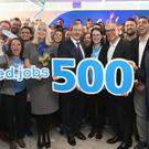 Taoiseach Enda Kenny poses with staff members at a press conference announcing 500 new jobs at recruitment company Indeed in Dublin