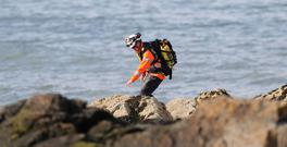 A member of the Irish coastguard searches the coastline in Skerries as a search and rescue operation is under way for a missing fisherman