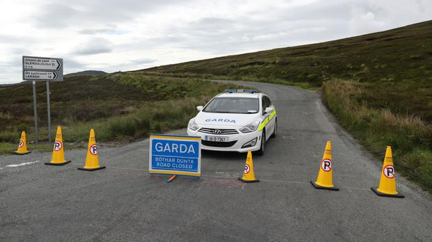 Garda close a road by the Sally Gap in the Wicklow Mountains after further human remains believed to be from a murdered young man have been found dumped in the area