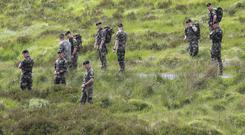 Defence Forces personnel assist Garda officers searching the Military Road area in the Wicklow Mountains after human remains were found