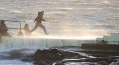 Dare devils run out to a diving board Salthill, Galway, Ireland, as Hurricane Ophelia batters the UK and Ireland with gusts of up to 80mph
