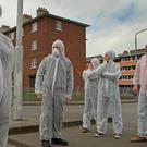 Residents of Dolphin House protest dressed in biohazard suits to illustrate problems with damp and sewerage