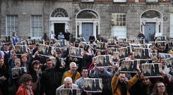 People take part in a protest outside 34 North Frederick St (Brian Lawless/PA)