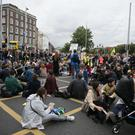 Demonstrators take part in a sit-down protest on O'Connell Bridge (Brian Lawless/PA)