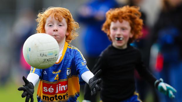 Nicholas Clarke, followed by his brother Victor, gathering a breaking ball during an under-sevens GAA charity match (Colm O'Neill/PA)