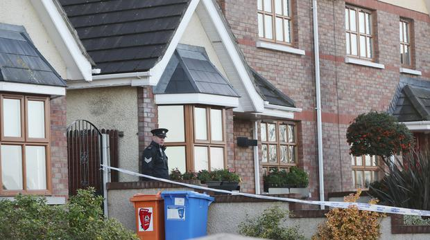 A Garda officer outside a house on the Clonmore estate in Ardee, Co Louth, where a woman's body was found (Niall Carson/PA)