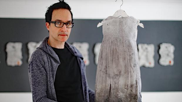 Curator Dino Notaro with a glass dress made by Alison Lowry, during a preview of the Stay With Me show (Niall Carson/PA)