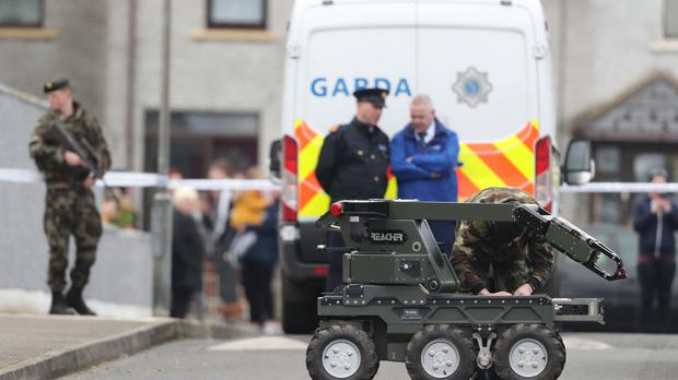 Gardai and an army bomb disposal robot at the scene of an unexploded bomb in the estate in Drogheda Co Louth (Niall Carson/PA)