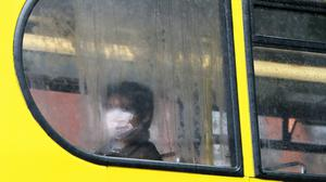 A person wearing a protective face mask sits on a bus in Dublin (PA)