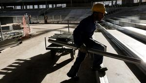 A building worker walks at the site of the Carioca Arena in Rio