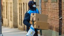 A worker wearing a protective mask and gloves carries Amazon.com Inc. boxes during a delivery in the Bronx borough of New York
