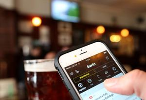 A gambler uses the Bwin.party mobile betting app on his phone