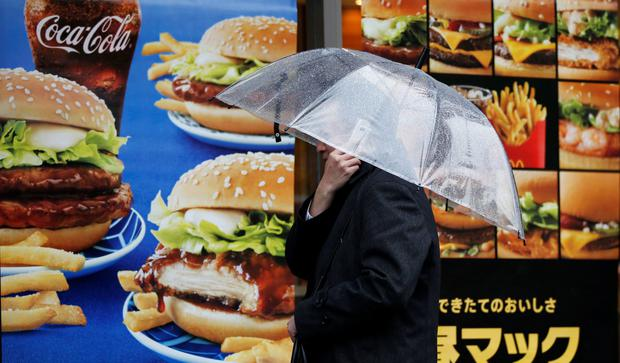 A man uses a mobile phone in front of a McDonald's restaurant in Tokyo