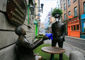 Closed: Face masks and rubber gloves on statues beside the Oliver St John Gogarty pub in Temple Bar, Dublin. PHOTO: GARETH CHANEY/COLLINS
