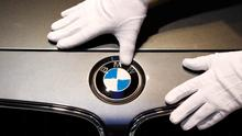 A man cleans a BMW logo before the annual news conference of German premium automaker BMW in Munich