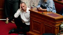 "Greek Finance Minister Yianis Varoufakis  (L) listens to Prime Minister addressing his MP's and ministers at the Greek Parliament in Athens on June 16, 2015. Tsipras accused international creditors of trying to ""humiliate"" the country and called on Europe to reconsider its support of harsh IMF reform proposals. .AFP PHOTO / LOUISA GOULIAMAKILOUISA GOULIAMAKI/AFP/Getty Images"