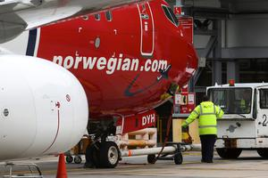 Members of the ground crew prepare to move an aircraft operated by Norwegian Air Shuttle at a departure gate at London Gatwick airport. Photo: Bloomberg
