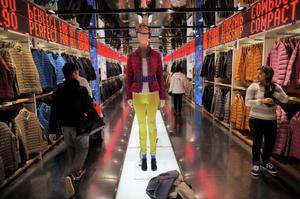 Customers shop for clothes at a Uniqlo store on 5th Avenue in New York