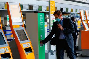 Clean break: A passenger uses a hand sanitizing unit beside Lufthansa self-service check-in machines in Frankfurt Airport