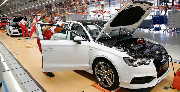 Factory workers inspect cars on the assembly line during the opening of a Audi factory in Budapest