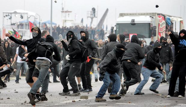 CLASHES: Protesters throw stones towards riot police during an anti-globalisation protest in the city of Rostock, Germany
