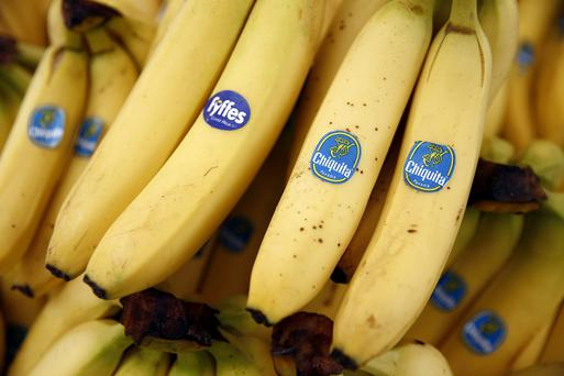 A bunch of Fyffes bananas, grown by Fyffes Plc, left, sits with bunches of Chiquita bananas, grown by Chiquita Brands International Inc., in this arranged photograph taken at a fruit and vegetable stall at an outdoor market in the Lewisham district of London, U.K., on Friday, Aug. 15, 2014. Chiquita, owner of the namesake banana label, said it will continue with its planned purchase of Irish competitor Fyffes after rejecting an unsolicited $611 million takeover proposal from Cutrale Group and Safra Group. Photographer: Simon Dawson/Bloomberg