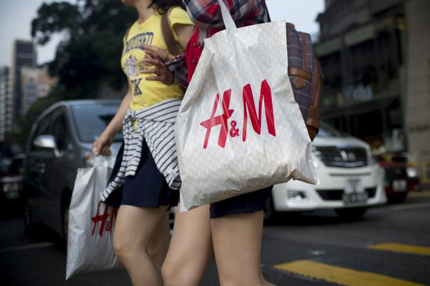 edestrians carrying Hennes & Mauritz AB (H&M) shopping bags cross Canton Road in the Tsim Sha Tsui area of Hong Kong, China, on Wednesday, Oct. 15, 2014. Hong Kong police said they would investigate a complaint alleging excessive use of force against a pro-democracy protester, after they used pepper spray and batons to retake a key road in seeking an end to an almost three-week occupation of parts of the city. Photographer: Brent Lewin/Bloomberg
