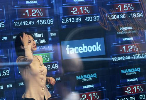A Nasdaq television reporter is seen inside the Nasdaq studios as the Facebook logo is displayed on a ticker board