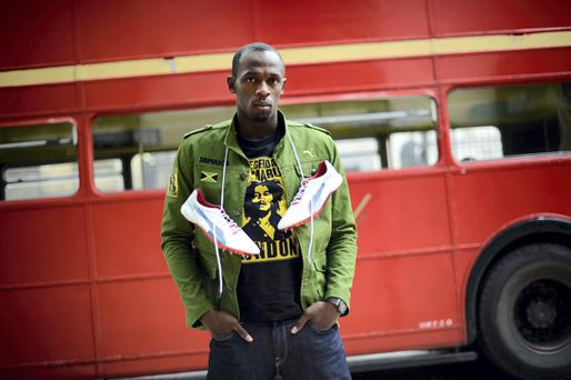Jamaican sprinter Usain Bolt poses with his running spikes for a Puma-arranged photo shoot in London