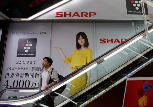 A man rides an escalator past Sharp Corp's advertisements at an electronics retail store in Tokyo in this October 31, 2013 file photo. Loss-making Sharp Corp has asked a domestic corporate turnaround fund to invest up to $250 million in capital - aid which would come on top of plans to tap its two main lenders for a second major bailout, the Nikkei business daily reported. REUTERS/Toru Hanai/Files (JAPAN - Tags: BUSINESS)