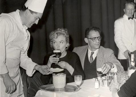 Marilyn Monroe samples an Irish Coffee in Shannon in 1956 as her husband Arthur Miller affects boredom.