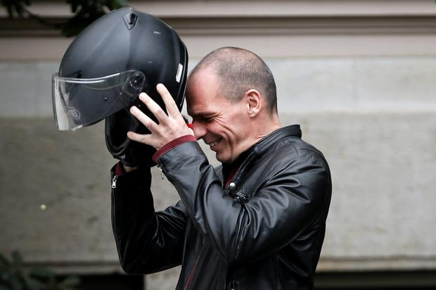 Greek Finance Minister Yanis Varoufakis wears his motorbike helmet following a meeting with Prime Minister Alexis Tsipras