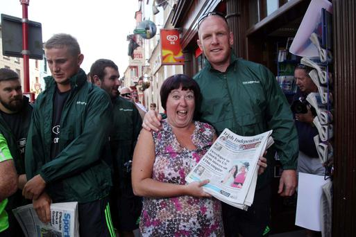 Mairead Cullinane of Meades Newsagents helps Munster Rugby Paul O'Connell sell Irish Independents outside Meades Newsagents, Clonakilty.