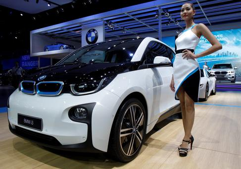A model poses beside a BMW i3 during a media presentation of the 36th Bangkok International Motor Show in Bangkok March 24, 2015. The Bangkok International Motor Show will be held from March 25 to April 5. REUTERS/Chaiwat Subprasom