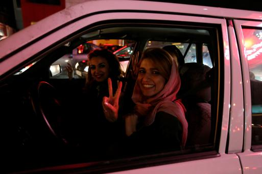 Women in a car flash the 'V for Victory' sign as they celebrate on Valiasr street in northern Tehran on Thursday night after the announcement of an agreement on the nuclear issue (Getty Images)